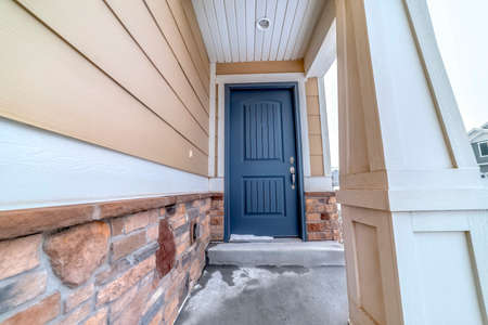 Home facade with blue panel door and melting snow on the doorstep and entryway. White column and wall with bricks and wood siding can also be seen at the exterior.