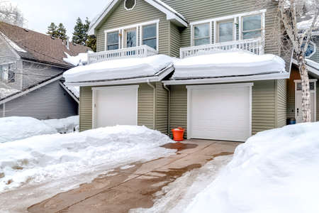Facade of home with snowy driveways in front of two car garage viewed in winter. Pitched roof, gray wall siding, and balconies can also be seen at the exterior of this house.