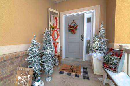Festive home entrance with christmas trees holiday decorations and basket wreath. Brick wall, gray front door and sidelight can also be seen at the facade of this house.