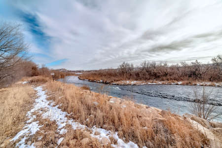 River with flowing water along grassy and rocky banks dusted with winter snow