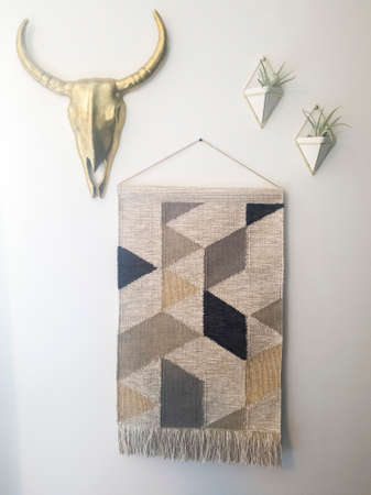 Woven tapestry metal bull head and plant hanger decorations against white wall. The woven wall hanger has a geometric pattern design and fringes.
