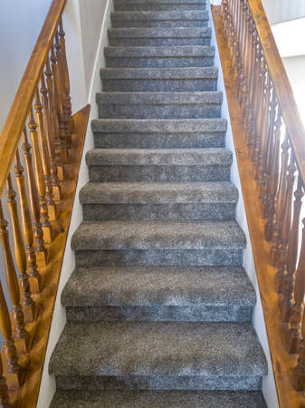Indoor staircase with carpeted treads and brown wooden handrails and balusters. Architectural views inside a home with close up of the stairway that leads to the upper floor. Banque d'images