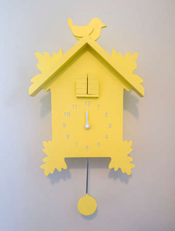 Close up of pastel yellow wooden cuckoo clock mounted on gray interior wall. A pendulum regulates this clock that strikes the hours with a sound like a common cuckoo's call.