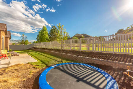 Trampoline at sunlit backyard of home with patio and planting bed against fence. The scenic neighborhood has a view of distant mountain and blue sky.