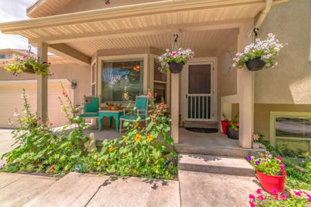 Home exterior with bay window on front porch decorated with flowers and plants. The entrance door and garage door can also be seen at the facade of this house. Stockfoto