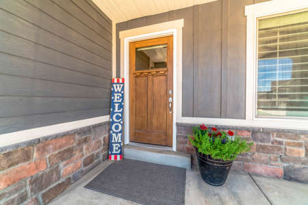 Brown front door with glass pane and Welcome sign against gray and stone wall. Gray doormat, potted plant with flowers, and window can also seen at the house entrance.