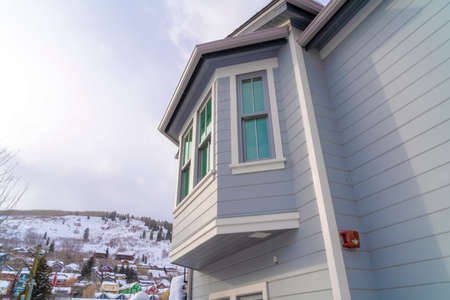 Home exterior in Park City Utah with bay window and gray horizontal wall siding. Colorful homes on a snowy hill against cloudy winter sky can be seen in the background.