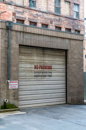 Corrugated metal garage door of an old brick building with No Parking sign. Entrance to the garage of a building with signages at the exterior wall. Stock Photo