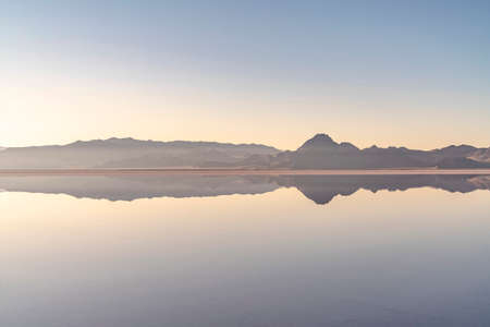 Sunrise and reflection at Bonnievale Salt Flats, Utah, USA with a glow on the horizon over mountain peaks