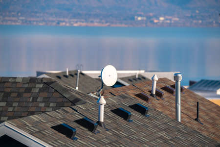 Television satellite dish mounted on a roof