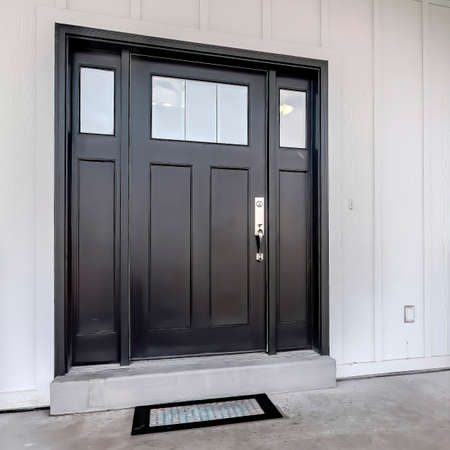 Square frame Home entrance with front porch and black front door against white panelled wall. Stairs leads to the entrance of this house with glass panes on the door.