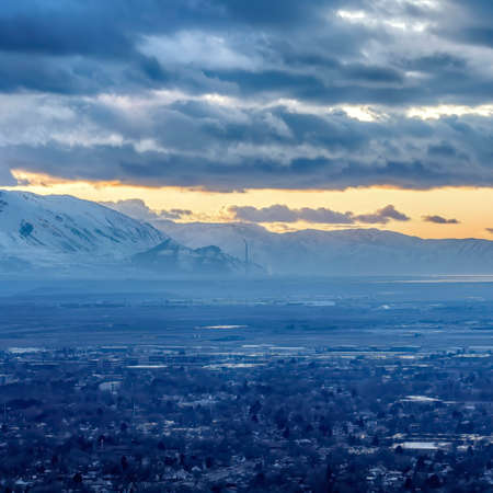 Square frame Salt Lake City Utah landscape against snowy mountain and cloudy sky at sunset. The city has a view of scenic nature and glowing golden sky. Stock Photo