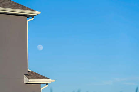 Close up of house exterior with blurry moon and blue sky in the background. The house has gray roof with white downspout at the edge of the wall.