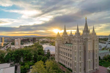 Salt Lake Temple and Salt Lake Tabernacle on scenic Temple Square at sunset. Downtown Salt Lake City with mountain and cloudy sky views can be seen in the background.