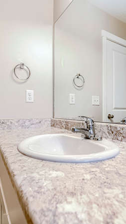 Vertical frame Top mount sink with stainless steel faucet on bathroom marble countertop. Wall mirror, towel rinf, electrical plug, light switch, and door can also be seen inside this room.