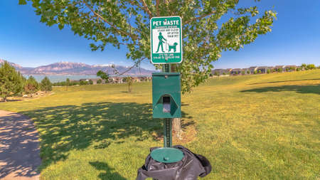 Panorama Dog poop bags and garbage can against timpanogos mountains and blue lake 写真素材