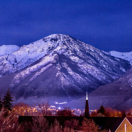 Square Snowy Wasatch Mountain towering over downtown Provo against blue evening sky. Scenic nature adn city landscape in Utah viewed at nighttime.