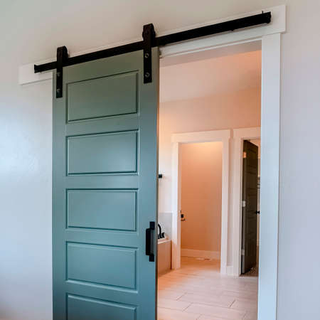Square frame Sliding gray wooden panel door that leads to the bathroom of a home. Bathtub and doorways can be seen inside the wash room.