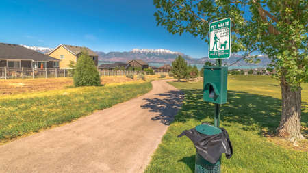 Panorama Pet Waste station with dog poop bags and garbage can beside a tree and pathway 写真素材