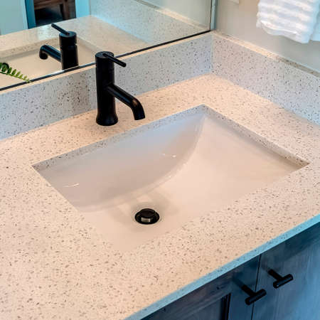 Square Bathroom white countertop with single basin undermount sink and black faucet. Cabinets, hanging towel, potted plant, and wall mirror can also be seen inside the room.