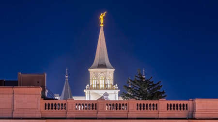 Panorama frame Provo City Center Temple with statue of angel and spire against blue evening sky. Exterior view of the temple of The Church of Jesus Christ of Latter-day Saints in Utah at night.