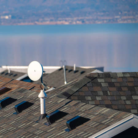 Square Television satellite dish mounted on a tiled house roof with selective focus and Utah Lake in the background
