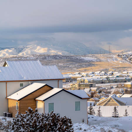 Square Homes in snowy Utah Valley neighborhood with scenic view of distant mountain. Thick gray clouds cover the vast sky on this cold day.