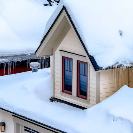 Square Close up of Park City Utah home with icicles and thick layer of snow on the roof. Dormers, icicles, and exetrior wall siding can also be seen in this winter scenery. Stockfoto