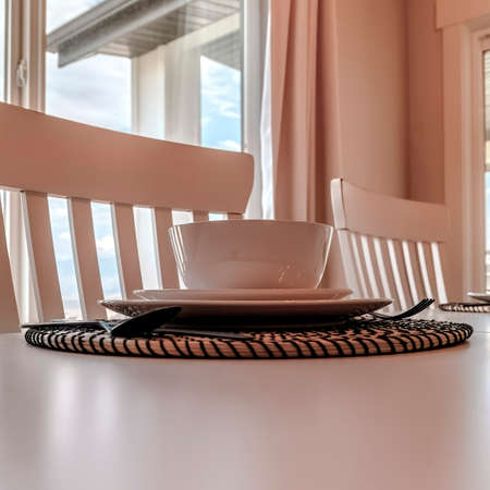 Square Tableware and utensils on woven placemat at the dining table with chairs Foto de archivo