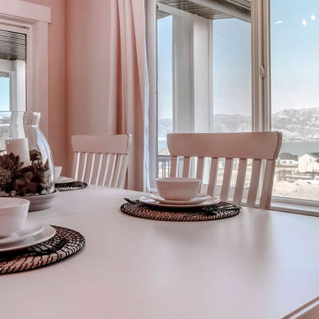 Square Home dining room with scenic view of snowy mountain and neighborhood in winter. The chairs, tableware, and woven placemats are arranged on the table with a centerpiece. Foto de archivo