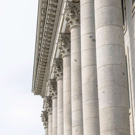 Square Corinthian stone columns at Utah State Capital Building facade in Salt Lake City. The massive columns stand on an exposed foundation podium at the pedimented entrance of the building. Foto de archivo