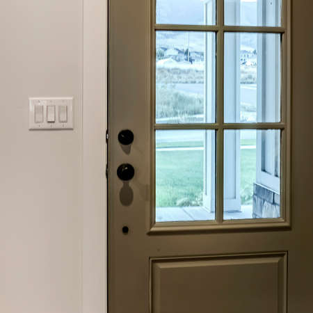 Square crop Hinged front door with glass pane viewed from interior of home with wood floor. Multiple rocker light switch is installed on the wall beside the doorframe.