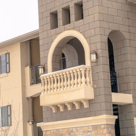 Square crop Apartment exterior with balconies and snowy roofs against cloudy sky in winter. Stone wall, moulded balustrade, and window shutters can also be seen in this residential building.