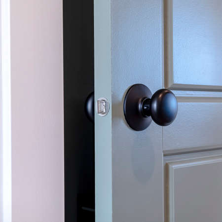 Square frame Gray paneled hinged wooden bedroom door with black door knob and visible latch. Close up view of a partially opened interior door with white doorframe. Banque d'images