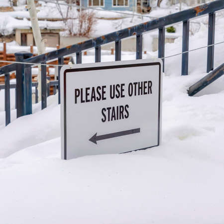 Square crop Stairs buried in winter snow with sign that reads Please Use Other Stairs Zdjęcie Seryjne