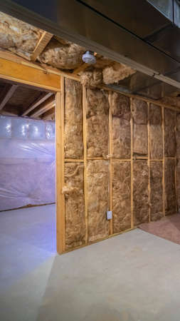 Vertical frame Insulation inside the room of a frame house under construction with moisture protection film, ventilation and electric communication systems installed
