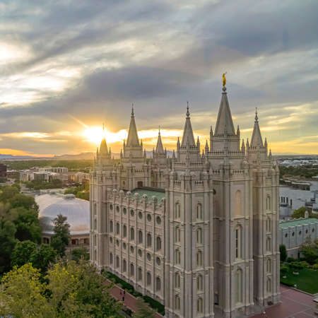 Square Salt Lake Temple and Salt Lake Tabernacle on scenic Temple Square at sunset. Downtown Salt Lake City with mountain and cloudy sky views can be seen in the background. Stock Photo