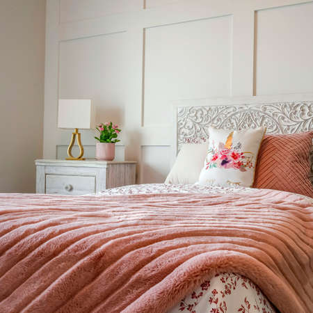 Square Bedroom with feminine beddings and decorative headboard against panelled wall. Side table with lamp and potted flowers can be seen beside the single bed.