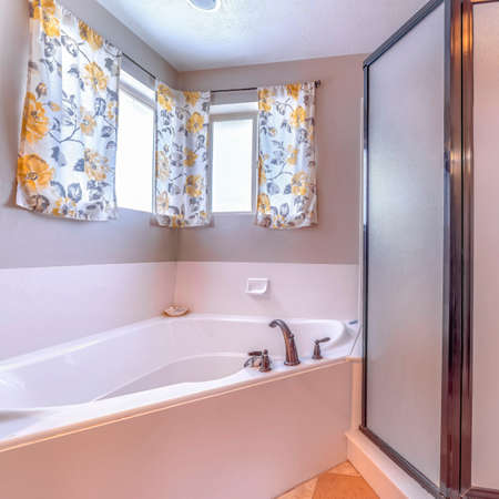 Square frame Bathroom built in bathtub and shower stall with framed frosted glass enclosure. colorful printed floral curtains hang against the window.