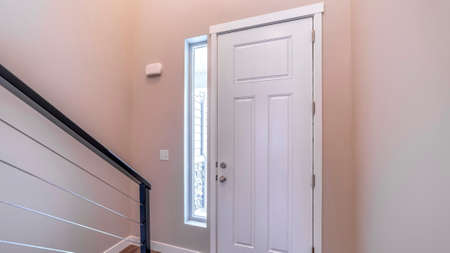 Panorama White hinged wooden front door and sidelight viewed from inside of home. Stairs handrail and brown wooden floor can also be seen at the interior of this house.