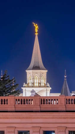 Vertical crop Provo City Center Temple with statue of angel and spire against blue evening sky