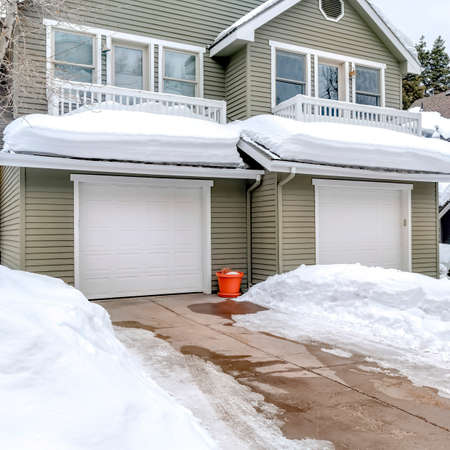 Square crop Facade of home with snowy driveways in front of two car garage viewed in winter. Pitched roof, gray wall siding, and balconies can also be seen at the exterior of this house.