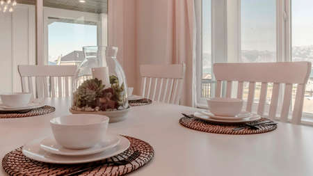 Panorama Dining table with tableware and woven placemat arranged around a centerpiece