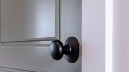 Panorama frame Gray wooden hinged door with black door knob and panels inside of home. Close up view of a paneled bedroom door with white doorframe.
