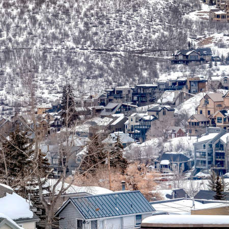 Square frame Park City Utah mountain in winter with colorful homes that sit on snowy slopes. The frosted landscape is abundant with lush evergreen trees.