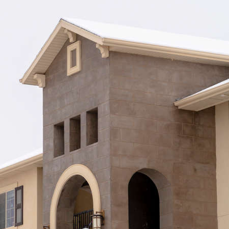 Square crop Beautiful apartments with arched balcony stone wall and snowy roof in winter. Residential building exterior with cloudy sky background on a cold day.