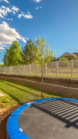Vertical Trampoline at sunlit backyard of home with patio and planting bed against fence. The scenic neighborhood has a view of distant mountain and blue sky. Stock Photo