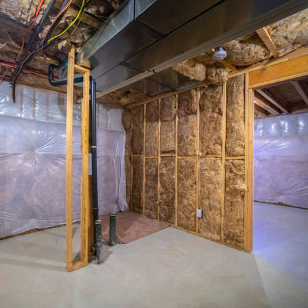 Square Insulation inside the room of a frame house under construction with moisture protection film, ventilation and electric communication systems installed