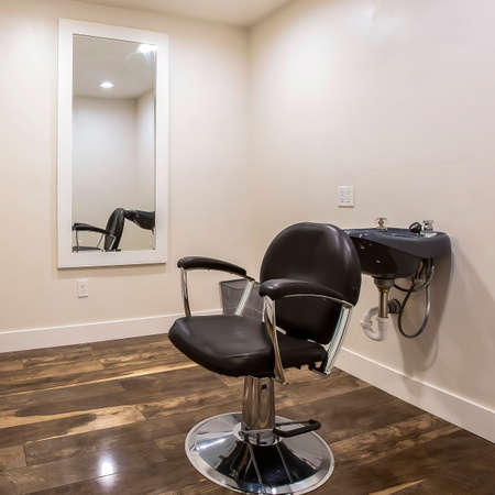 Square frame Hairdresser chair and backwash shampoo bowl inside salon with bench and mirror. The styling room has white wall and brown wooden floor. Stock fotó