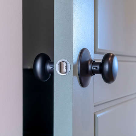 Square frame Partially opened home bedroom hinged wooden gray door with black door knob. The latch bolt is protruding at the side of the interior door. Standard-Bild